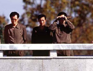 North Korean leaders standing on balcony and looking through binoculars.